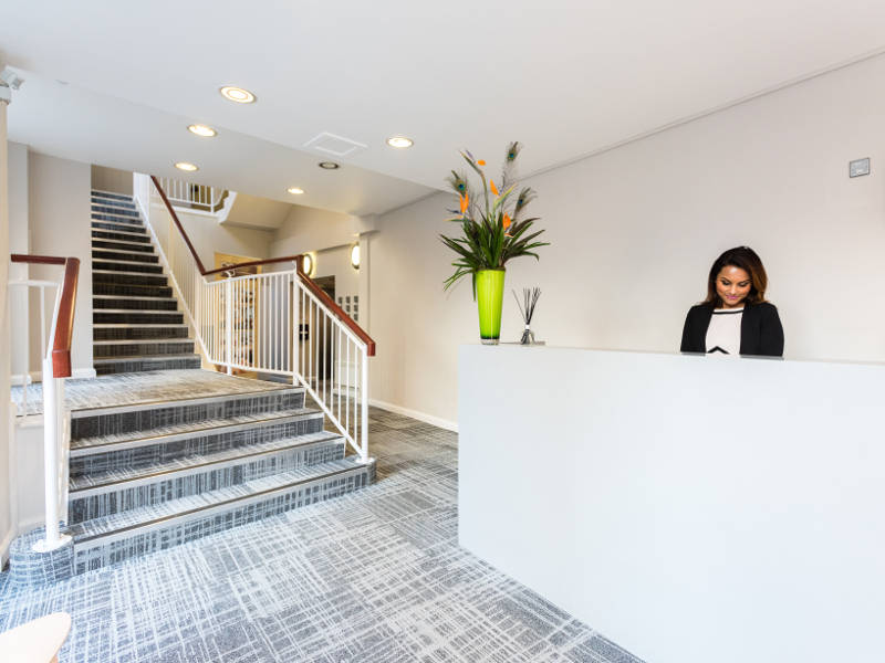 A friendly receptionist at reception in PREMIER SUITES Reading