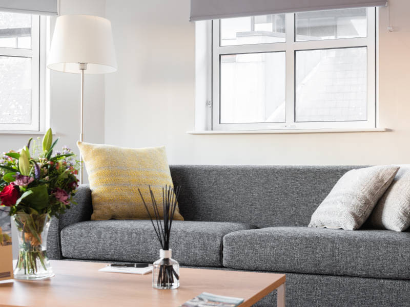 A grey couch in the living area of PREMIER SUITES Reading serviced apartments