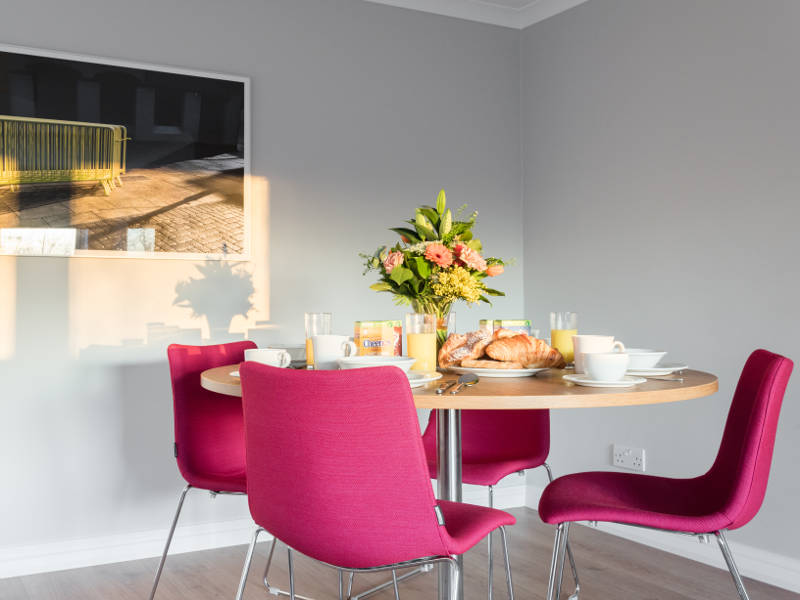 The dining table set up for breakfast in PREMIER SUITES Reading serviced apartments