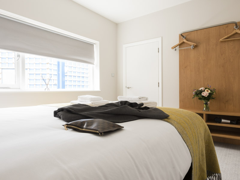 Guests belonging on the bed in PREMIER SUITES Reading serviced apartment